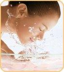 mujer joven salpicando su cara con agua